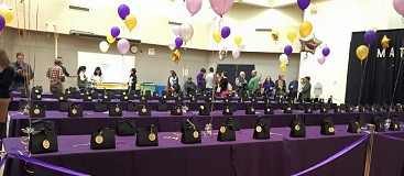 Balloons and gift bags on a purple table for Match Day